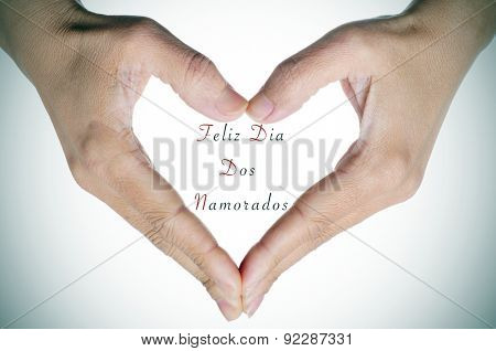 woman hands forming a heart and the text Feliz Dia Dos Namorados, written in portuguese, to congratulate for the holiday for lovers in Brazil
