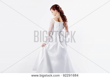Beautiful bride in wedding dress, back, white background