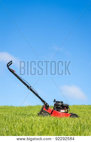 Lawn mower green grass blue sky
