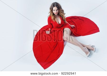 Fashion Photo Of Young Magnificent Woman In Red Dress.  Girl Sitting On The Floor