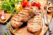 stock photo of veal  - Grilled veal steaks with vegetables on cutting board - JPG