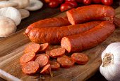 image of charcuterie  - Delicious merguez sausages on a rustic tabletop with pita garlic and tomatoes - JPG