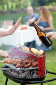 stock photo of frazzled  - Person refusing beer on party in garden - JPG