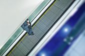 foto of escalator  - Legs of businessman with briefcase ascending on escalator - JPG