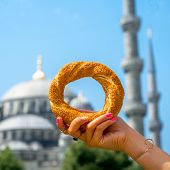 picture of bagel  - Holding turkish bagel with Blue Mosque on background - JPG