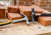 stock photo of brick block  - Mason bricklaying background with two  hammers  and clay brick blocks - JPG
