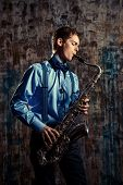 foto of sax  - Young expressive musician playing the saxophone - JPG