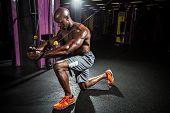 stock photo of chest  - Muscular body builder working out  at the gym doing chest fly exercises on the cable wire machine - JPG