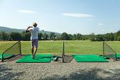 picture of swing  - Athletic golfer swinging at the driving range dressed in casual attire - JPG