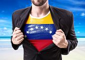 picture of civil war flags  - Businessman stretching suit with Venezuela flag on beach background - JPG