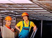 pic of suspenders  - Men in builder uniform installing suspended ceiling - JPG