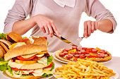 stock photo of high calorie foods  - Body part of woman eating pizza at table - JPG
