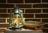 stock photo of kerosene lamp  - Burning kerosene lamp and books on brick wall background - JPG