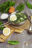 stock photo of sorrel  - Sorrel soup with egg on wooden table - JPG