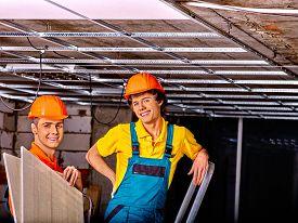 picture of suspenders  - Men in builder uniform installing suspended ceiling - JPG
