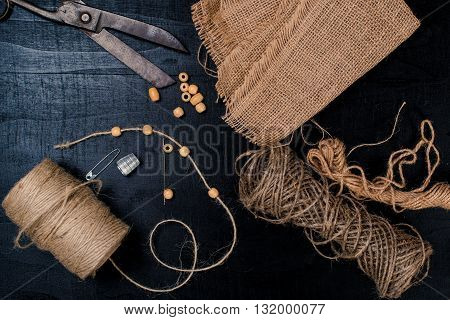 Set for needlework: scissors linen fabric with a rope on a black background. Top view.
