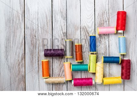 Spools of threads on the white wooden background.