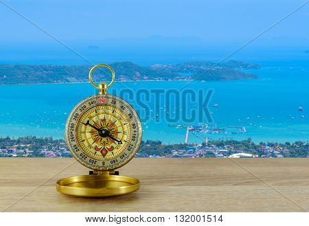 Compass on wooden table with blurred viewpoint andaman sea background.