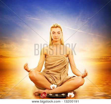 Young beautiful woman meditating in a sea at sunset