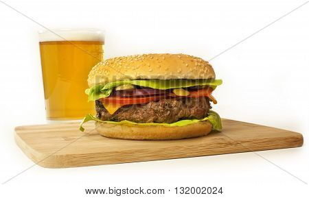 Photo of burger with leaves of green lettuce slices of Cheddar cheese gherkins red onions tomatoes and thick meat patty on wooden board with blurred glass of beer in background on white