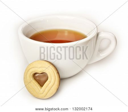 A white cup of tea with a butter cookie with a chocolate filling heart shape in the middle on white background