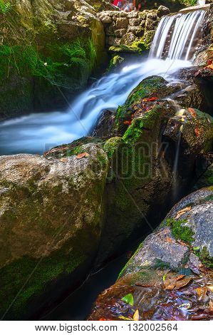 Waterfall in the deep woods of the jungle. Round stones with green moss in the mountains of Thailand