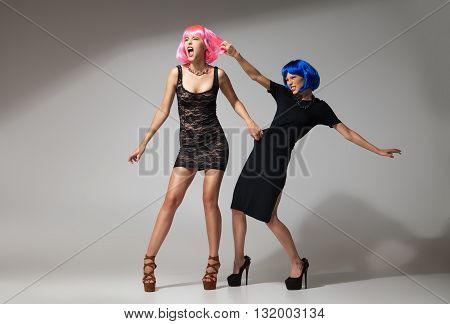 Fashion battle of two models in bright wigs and black dresses.Studio shot