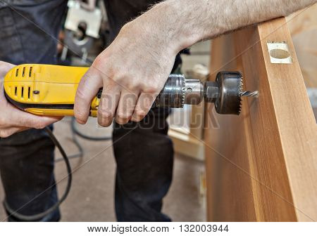 Door installation hands carpenter holding yellow power drill with wood hole saw drill bit drilling through the door to set the lock with a handle close-up.