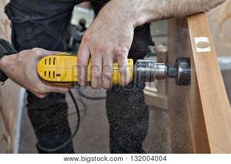 Hands woodworker with yellow electric drill boring large hole of door lock using hole saw drill bits sawdust flying around close-up.