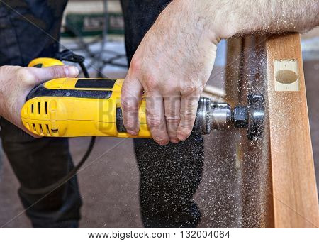 Install interior wooden door doorknob lock using hole saw to begin cutting hole for deadbolt close-up.