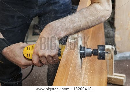 Door installation Install door lock use hole saw to begin cutting hole for deadbolt close-up carpenter hand holds yellow electric drill.