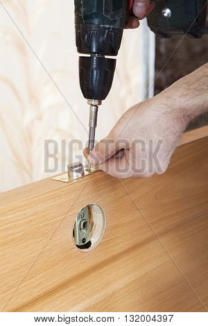 Installation door knob with lock woodworker screwed screw using screwdriver.