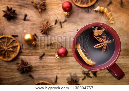 cup of mulled wine with orange, cinnamon stick, star anise, cloves and christmas balls
