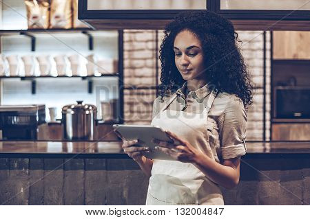 Checking all updates. Young African woman in apron using her digital tablet while standing at bar counter