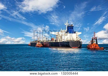Tugboats towing a tanker ship at sea.
