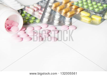 Colorful tablets in blisters and bottle on table in close-up