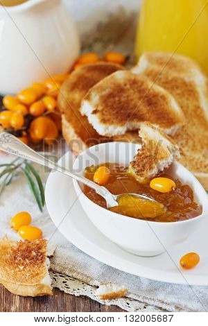 Homemade sea buckthorn jam toast and ripe sea buckthorn berries on the table. Healthy breakfast. Bio healthy food. Selective focus