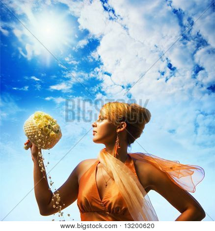 Beautiful redhead girl with a bouquet of flowers over cloudy sky