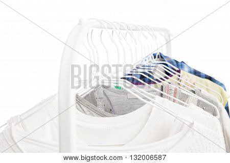 Metal rack with clothes hanging. Isolated over white