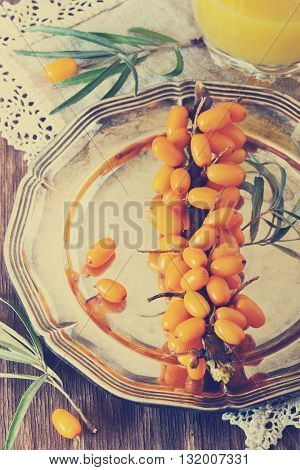 Organic ripe sea buckthorn in vintage metal plate on a wooden background. Bio healthy food. Selective focus. Top view. Tinted image of a retro style