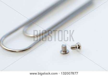 Screws and clip / Two small screws next to the paper clip