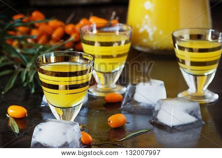 Traditional alcoholic cocktail of sea buckthorn berries on a granite background. Alcoholic beverages from different countries. Pernicious drinks. Selective focus