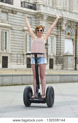 young attractive tourist woman with red hair wearing shorts and summer singlet riding happy electrical segway having fun driving free hand in touristic city tour in Madrid royal palace in Spain
