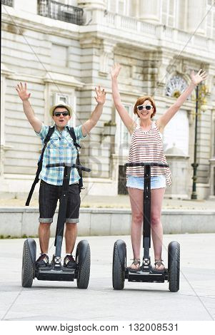 young happy tourist couple riding segway enjoying city tour in Madrid palace in Spain having fun driving together on funny and romantic summer holiday in urban transport concept