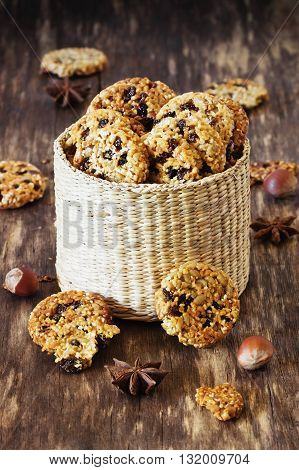 Homemade cookies from sesame seeds raisins and caramel in a basket on a wooden background. Selective focus