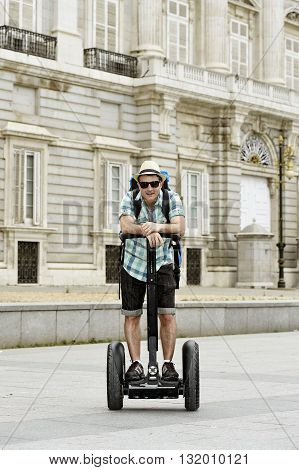 young happy tourist man with backpack riding city tour segway driving happy and excited visiting Madrid palace in Spain having fun in urban transport concept