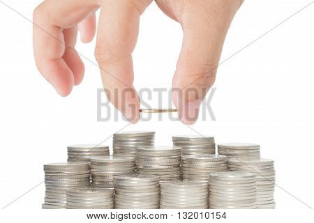 Hand put gold coin to stack of coins isolated on white background for concept success in business or finance