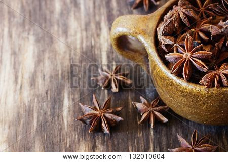 Star anise spice fruits and seeds in ceramic bowl on the vintage wooden background. Close-up. Selective focus. Rustic style. Copy space for you text
