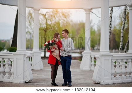 Marriage Proposal. Man And His Girlfriend With Bouquet Of Flowers Stay Near White Arch Of Love