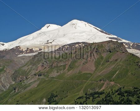 Snow-covered top of Elbrus on a background of blue sky.